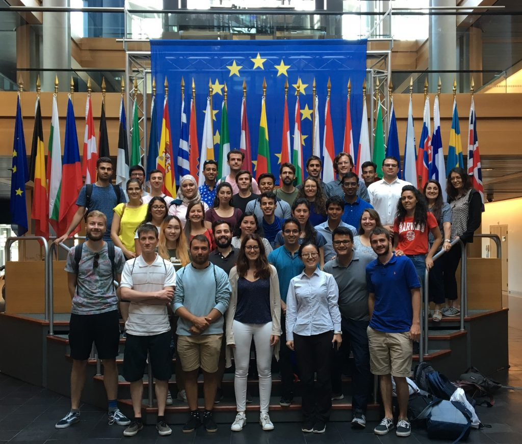 Group photo of students in front of the flags of the European Union in the European Parliament